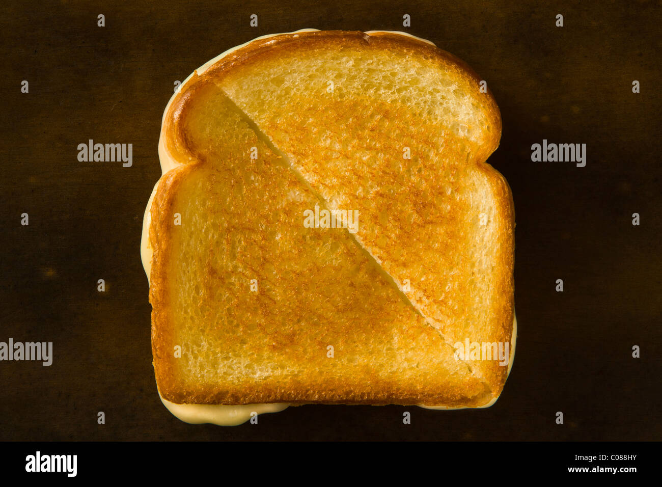 A Grilled Cheese Sandwich cut in half diagonally pulling the cheese on a wood table - Stock Image