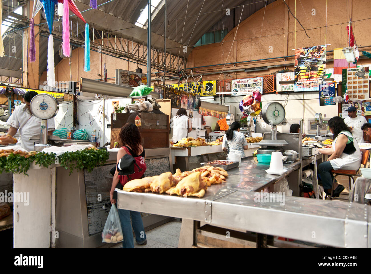 busy chicken butchers working at counters in lofty well lit interior of Medellin Market Roma district Mexico City - Stock Image
