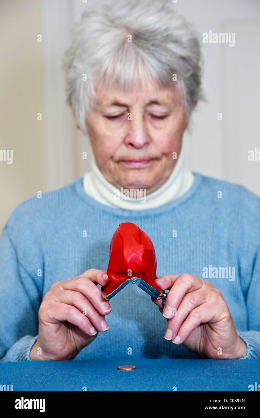 Poor senior elderly woman pensioner on small state pension with no money and a sad expression emptying a penny coin - Stock Image