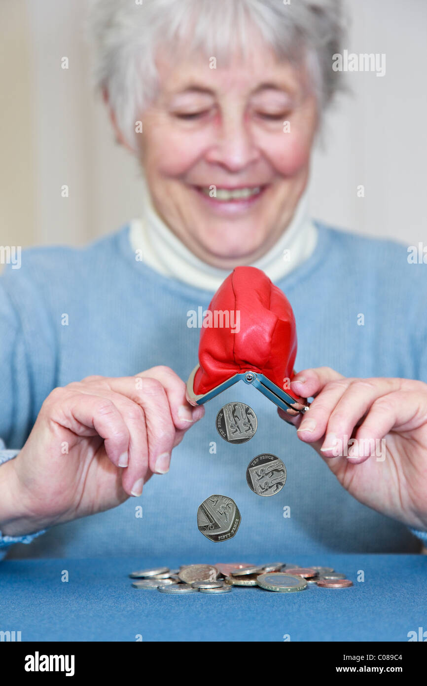Composite of a wealthy senior elderly pensioner OAP lady retiree with a pleased expression emptying a pile of money - Stock Image