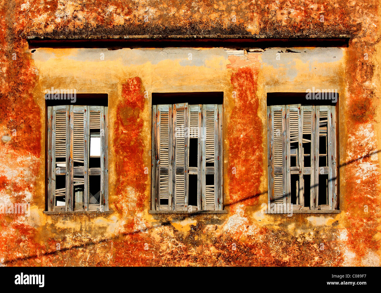 An old timeworn facade of an old house with broken windows in the old town of Rethymnon, Crete, Greece - Stock Image