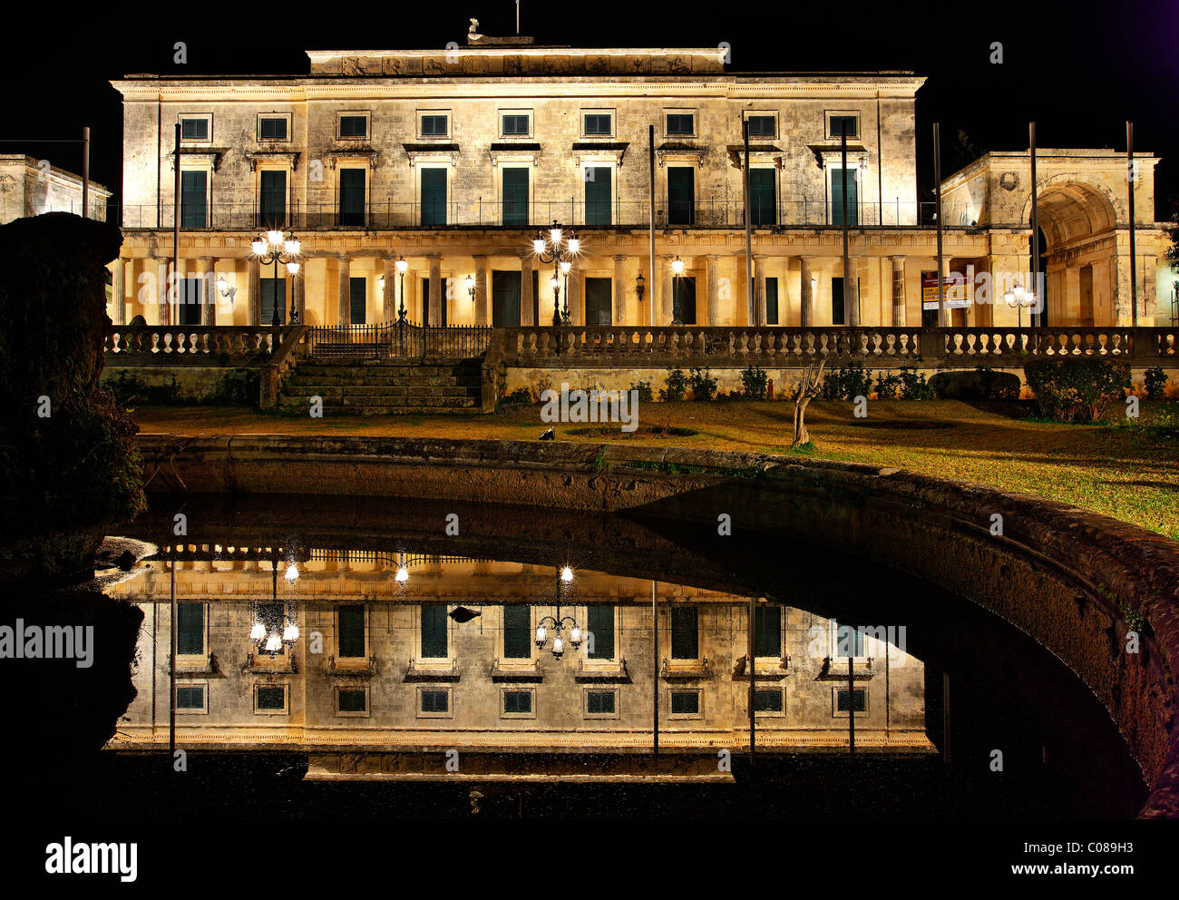 The 'Palace of Saints George & Michael' at the edge of Spianada and Liston, reflected in a fountain. - Stock Image