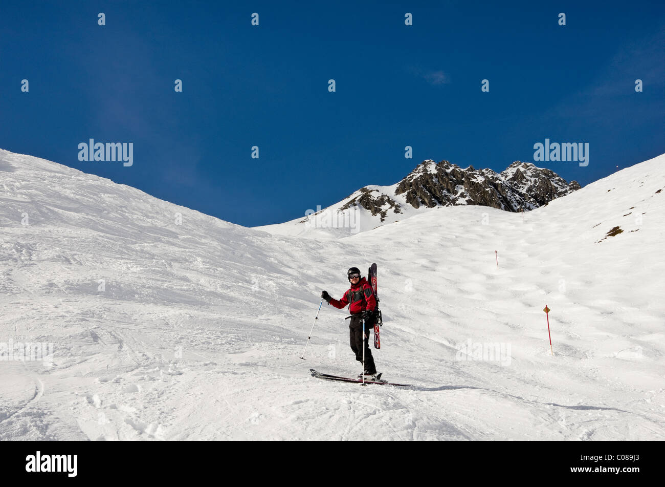 St Anton am Arlberg, Tyrol, Austria. Skier carrying skis on ski route 33 from Kapall in Austrian Alps. - Stock Image