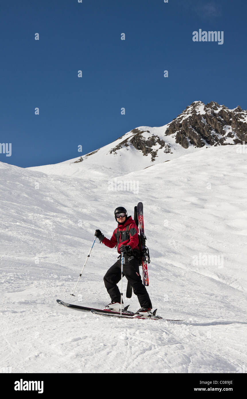 St Anton am Arlberg, Tyrol, Austria, Europe. Skier carrying skis on ski route 33 from Kapall in Austrian Alps. - Stock Image