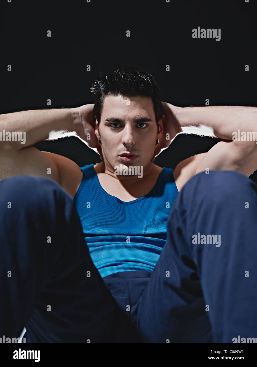 young adult caucasian male in blue sportswear exercising abdominals on black background, looking at camera. Stock Photo