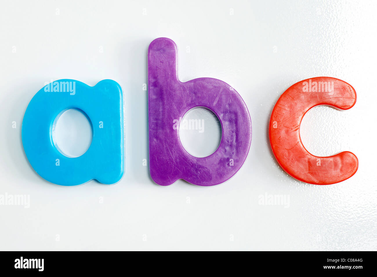 Fridge magnet: colorful plastic alphabet letters on textured white refrigerator. Stock Photo