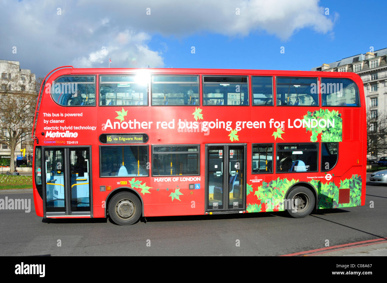 Sun glint off side of green electric hybrid public transport double decker London red bus operated by Metroline - Stock Image