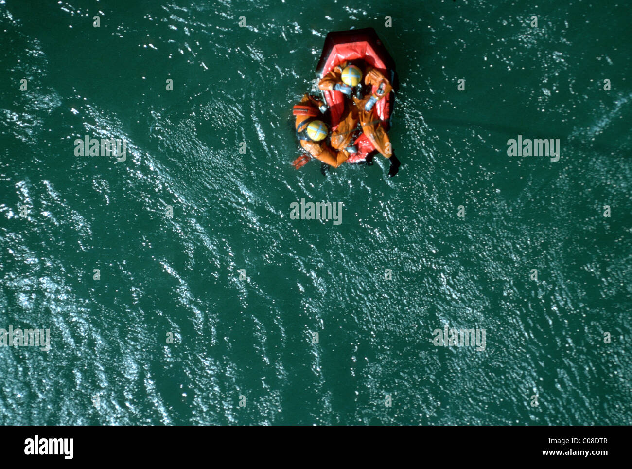 Search and rescue with casualty being winched up to a helicopter - Stock Image