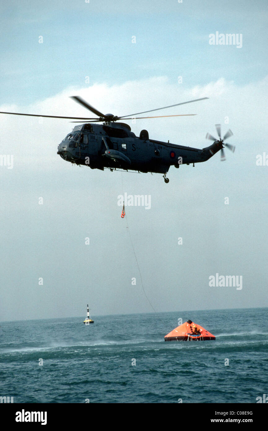 Helicopter coming to the rescue of men in a dinghy at sea - Stock Image