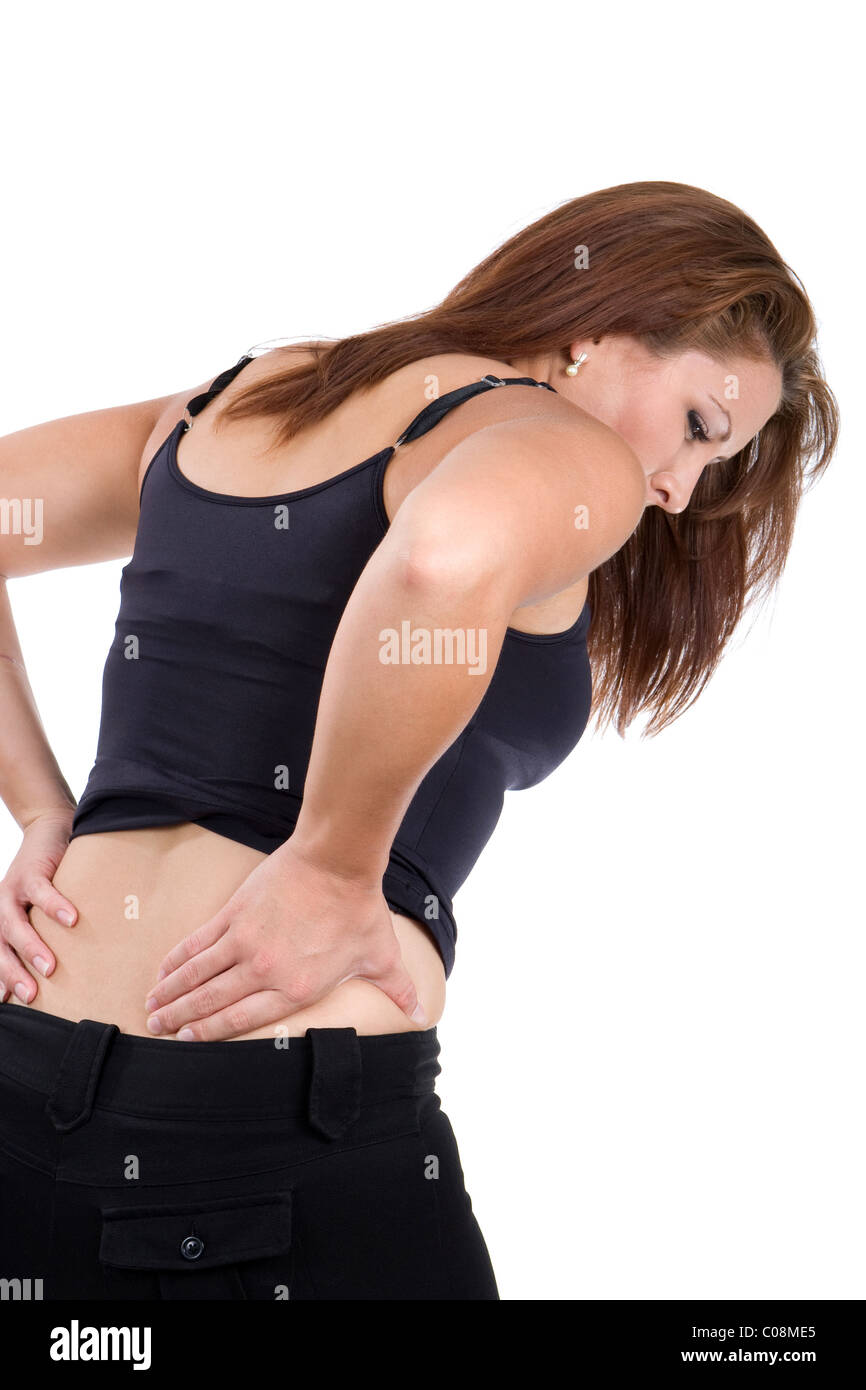 Woman bends over in pain rubbing her lower back as a result of a spinal injury accident. - Stock Image
