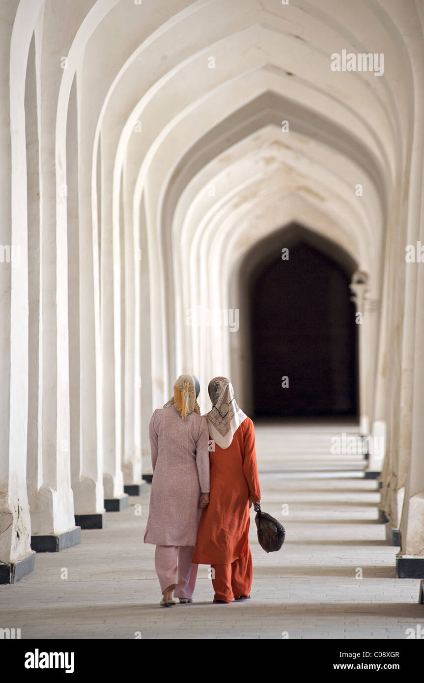 Uzbeki women walking down a vaulted corridor, Kalon Mosque, Bukhara, Uzbekistan - Stock Image