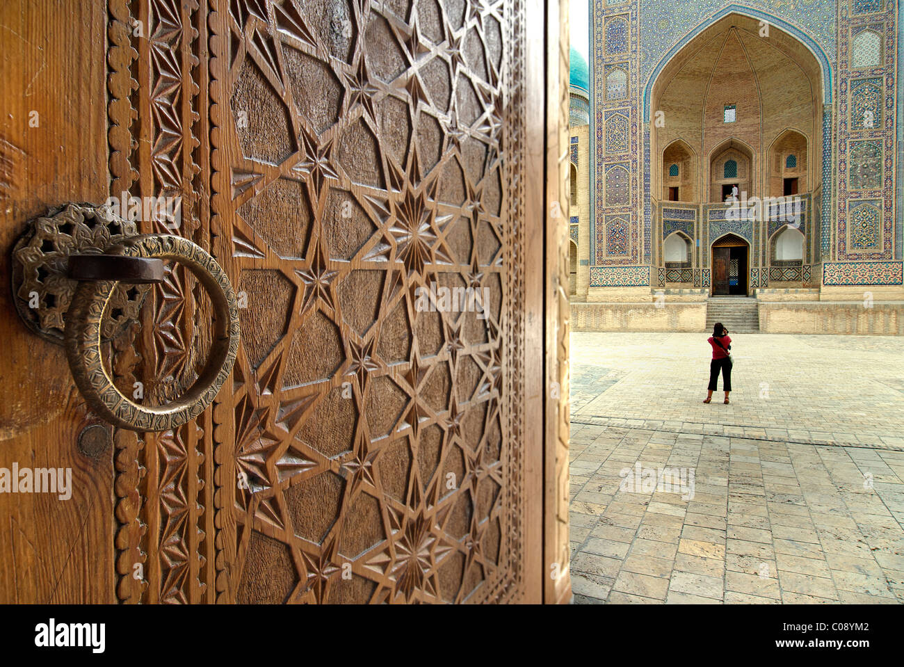 The Mir-i-arab Madrassah seen beyond the ornate carved doors of the Kalon Mosque, Bukhara, Uzbekistan - Stock Image