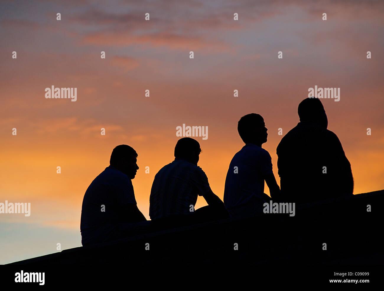 Group of 4 Uzbeki men silhouetted against the sky at dusk, Bukhara, UzbekistanStock Photo