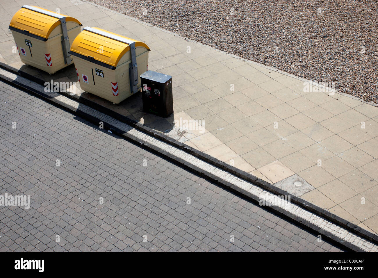 Two yellow public waste bins and a little black bin on the seafront in Brighton, East Sussex. - Stock Image