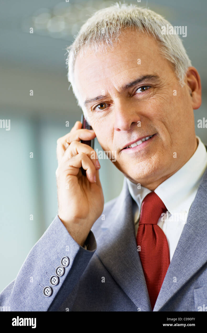 portrait of mature business man talking on the phone, looking at camera and smiling. Stock Photo