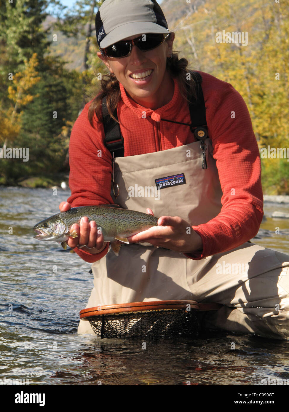 Woman holds and shows off a Rainbow Trout caught while fly fishing on the Russian River, Kenai Peninsula, Southcentral - Stock Image