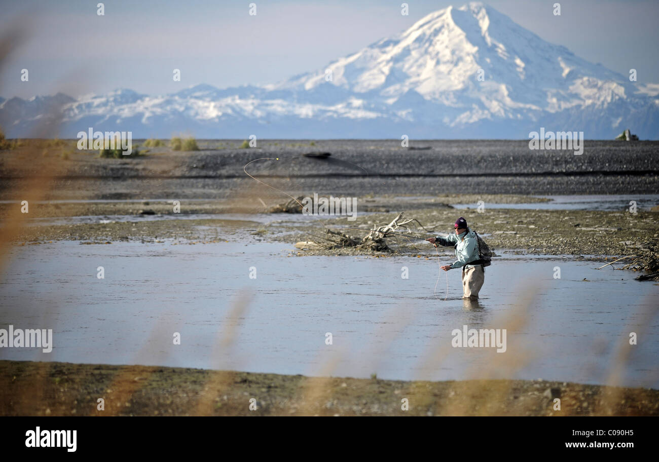 Woman fly fishing for wild Steelhead on Deep Creek with Mt. Redoubt in the background, Kenai Peninsula, Southcentral - Stock Image