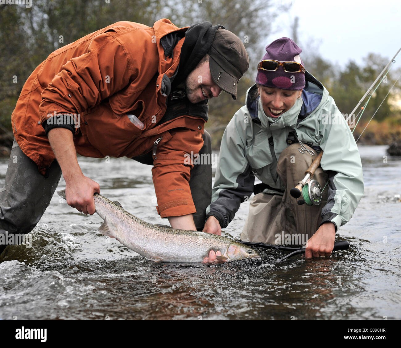 Man and woman kneeling in water to show off a wild Steelhead caught in Deep Creek, Kenai Peninsula, Southcentral - Stock Image
