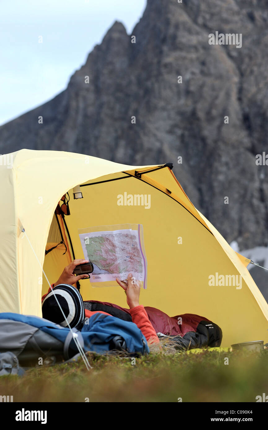Woman in a tent consults a GPS and map while camping at Rabbit Lake, Chugach State Park, Southcentral Alaska, Autumn Stock Photo
