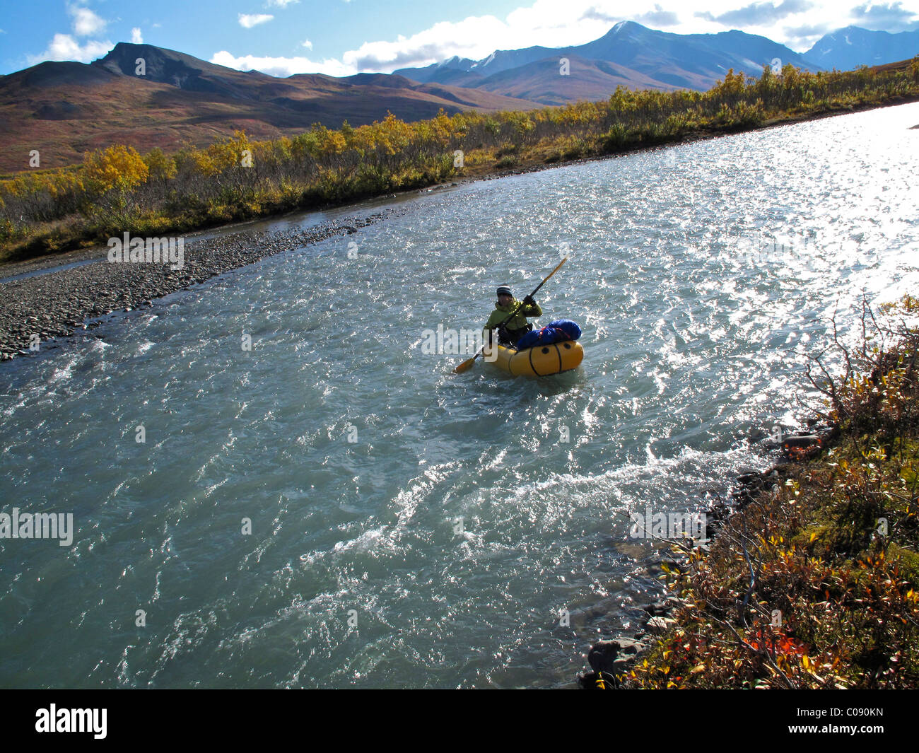 Woman packrafts down the Sanctuary River in Denali National Park, Interior Alaska, Autumn Stock Photo