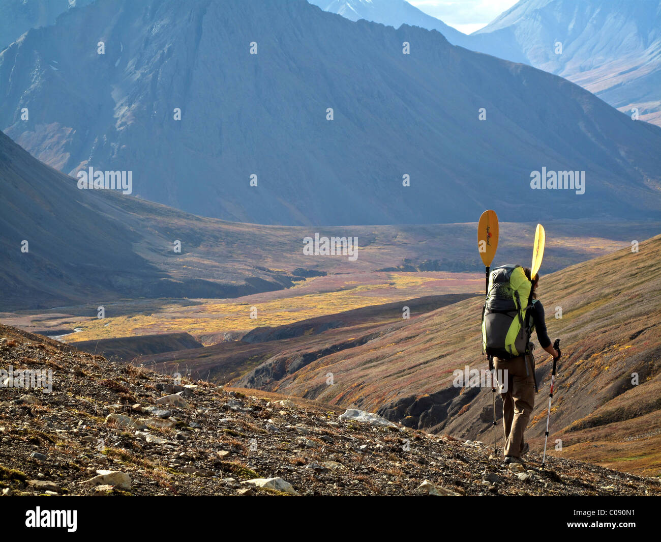 Female backpacker with a packraft enjoys view along the trail to the headwaters of Sanctuary River, Interior Alaska, - Stock Image