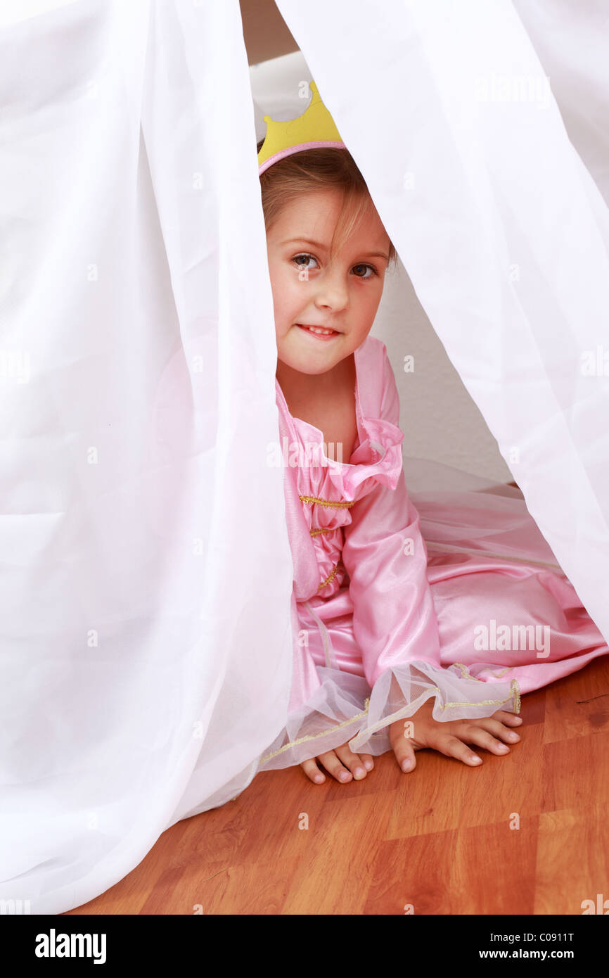 Adorable girl dressed as princess playing hide-and-seek at home - Stock Image
