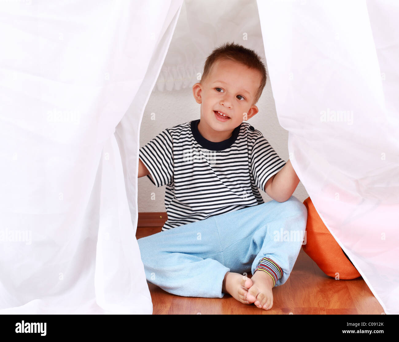 Adorable boy playing hide-and-seek at home - Stock Image