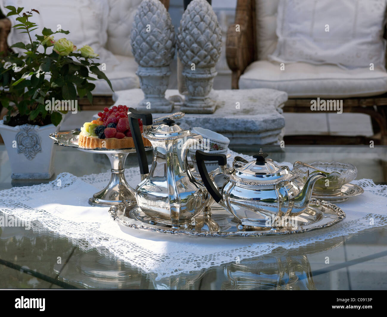 Luxuriously set coffee table with silver coffee and tea pots, and a fruit pie on a silver cake plate - Stock Image