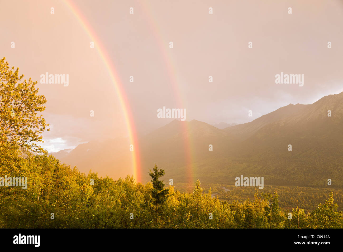 Sunset view of a double rainbow arching over Eagle River Valley after a passing storm, Southcentral Alaska, Summer - Stock Image
