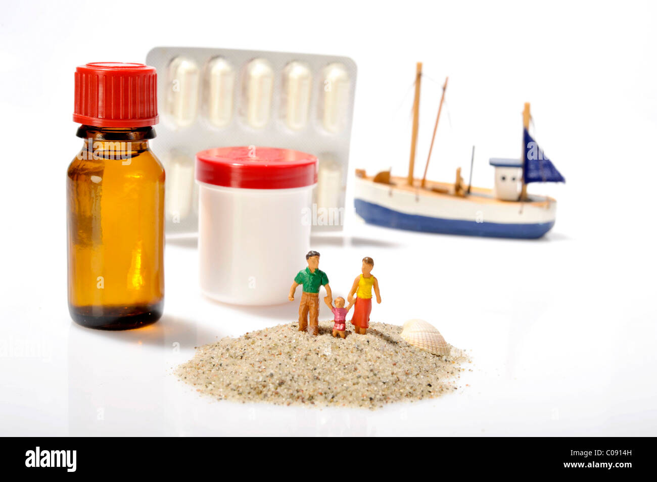 Family figurines in sand in front of medicaments from a first aid kit, symbolic image - Stock Image