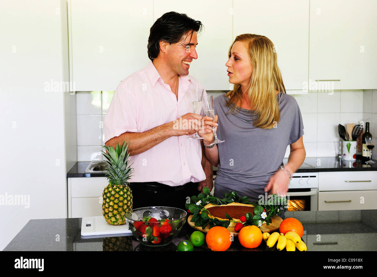Young couple clinking glasses, dessert and fruit in the foreground Stock Photo