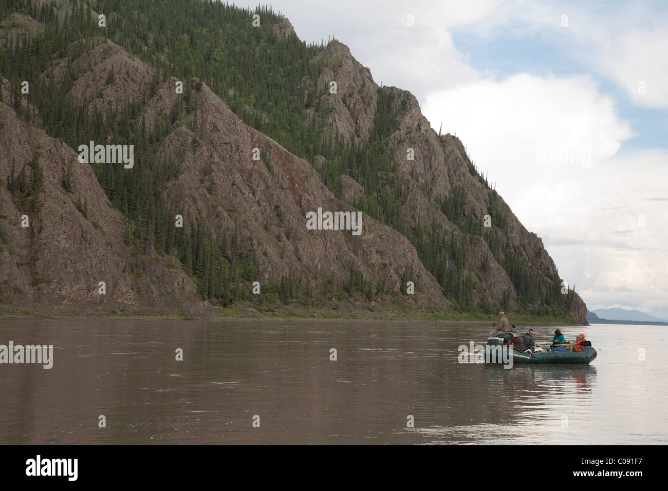 Family floats by a large rock formation along the Yukon River, Yukon-Charley Rivers National Preserve, Interior - Stock Image