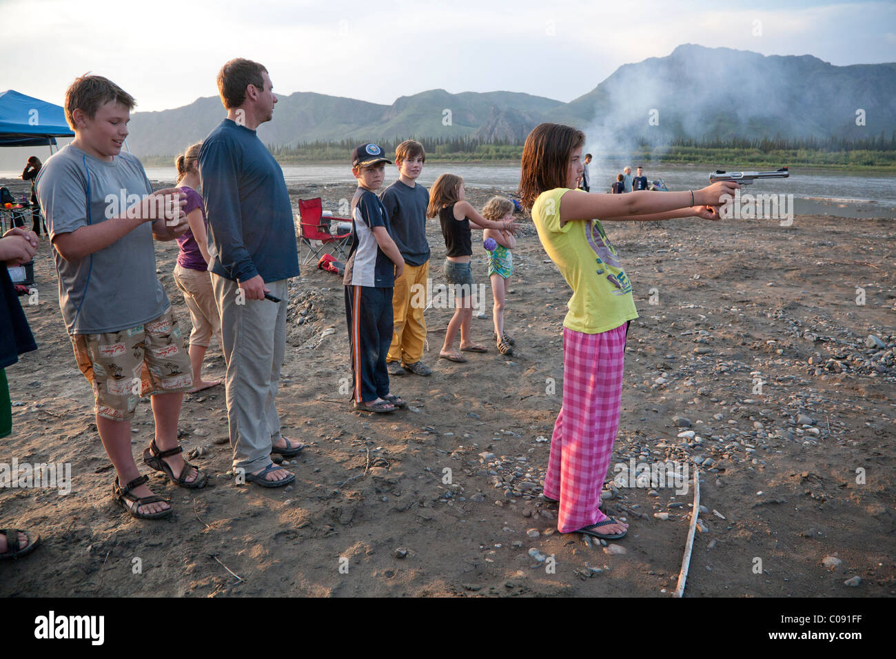 Young girl shoots a pistol in her pajamas and flip-flops at the edge of the Yukon River, Yukon-Charley Rivers National - Stock Image