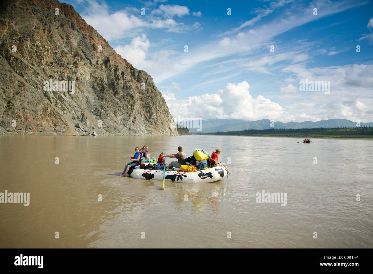 A family floats in a raft near the village of Eagle on the Yukon River, Interior Alaska, Summer - Stock Image