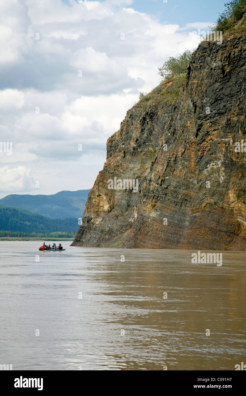 A family floats in a raft along Calico Bluffs near the village of Eagle on the Yukon River, Interior Alaska, Summer - Stock Image