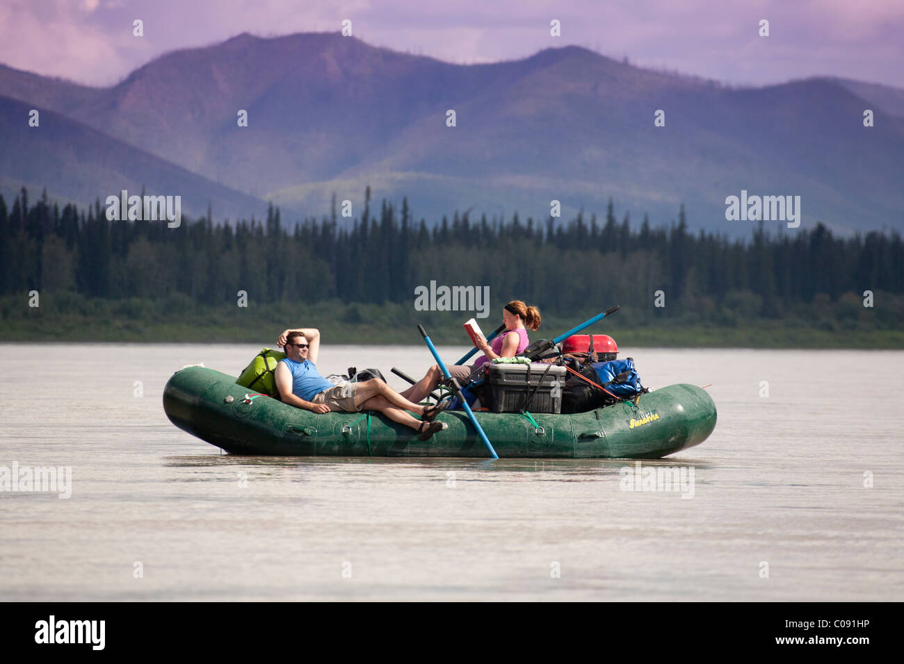 Two enjoy the day with reading a book and napping on a Yukon River raft float trip in Yukon Charley-Rivers National - Stock Image