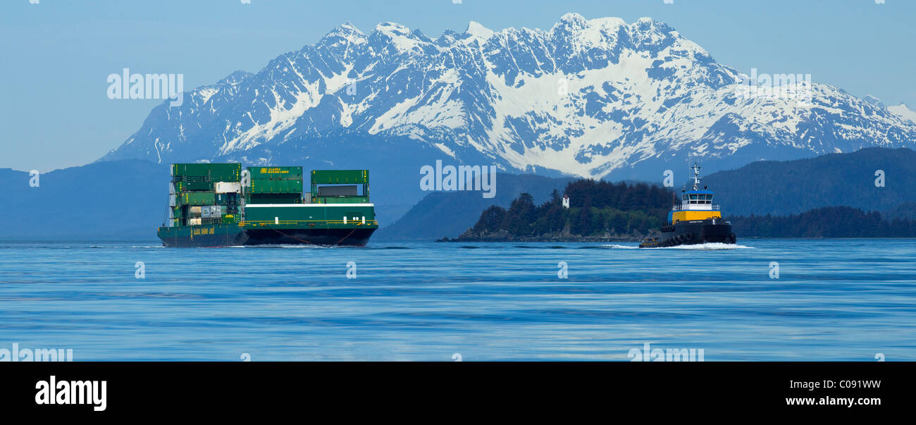 A tug pulling a barge cruises through the Inside Passage on its way south from Skagway, Alaska. Lynn Canal, Alaska - Stock Image