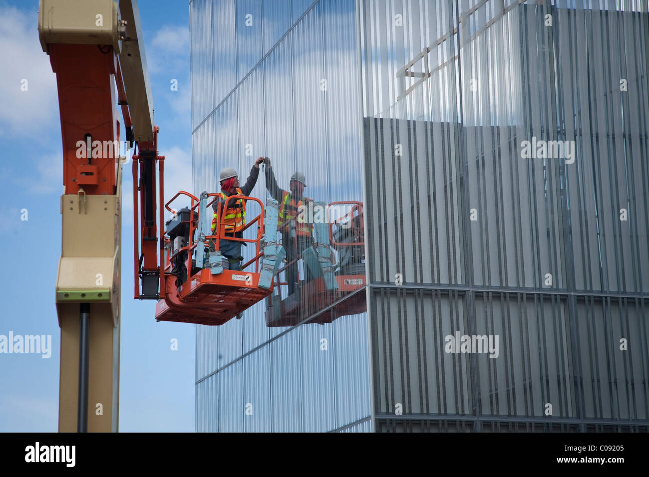 Male glazer installs glass on the exterior of the Anchorage Museum addition during construction, Anchorage, Alaska - Stock Image