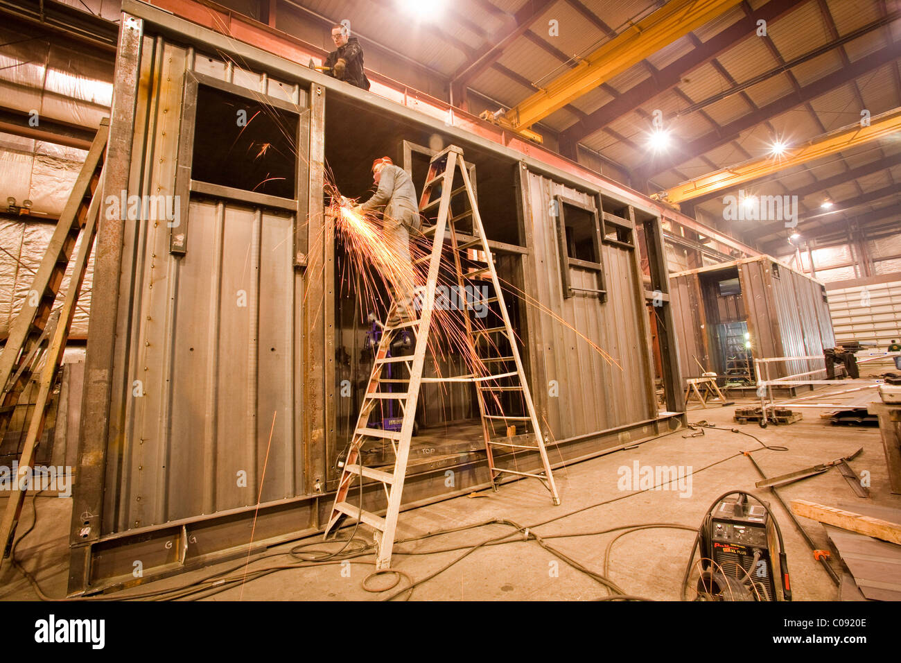 Welders working on a steel fabrictaion structure at Steelfab in Anchorage, Southcentral Alaska, Winter - Stock Image