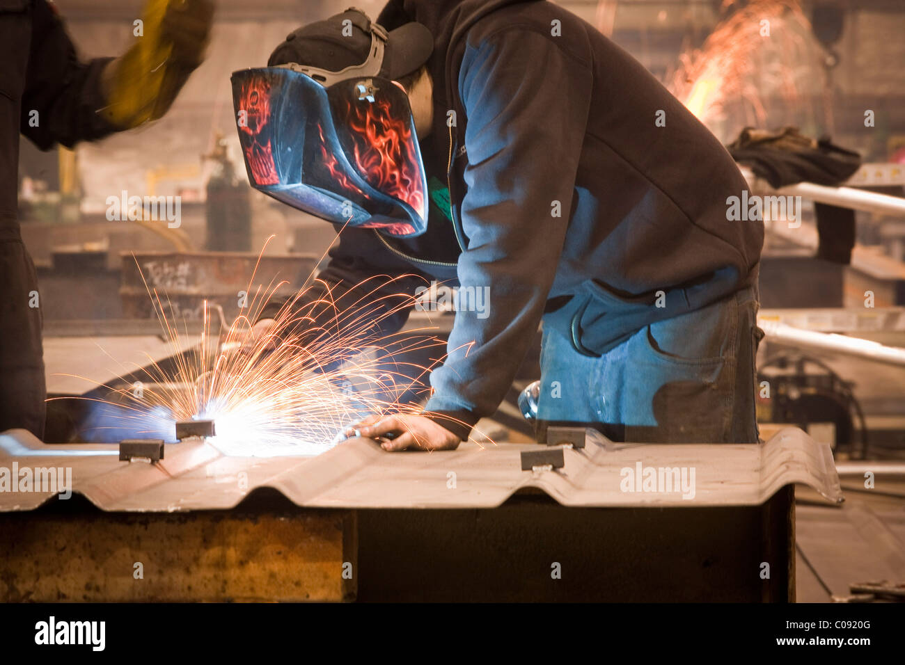 View of welder working on a steel fabrictaion structure at Steelfab in Anchorage, Southcentral Alaska, Winter - Stock Image