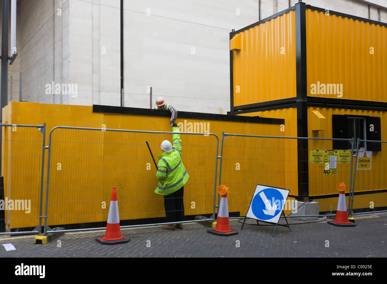 A construction site workman passes an item to his colleague by yellow temporary container offices. - Stock Image