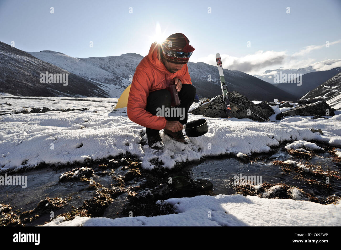 Backpacker fills pan with water from a creek at an alpine camp below Mt. Chamberlin, Brooks Range, ANWR, Arctic - Stock Image