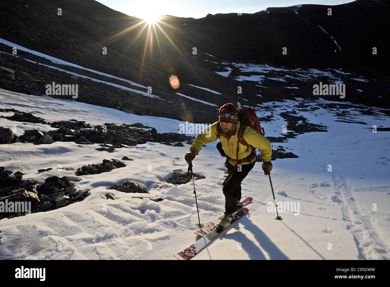 Backcountry skier makes an early morning ascent of the north side of Mt. Chamberlin, Brooks Range, ANWR, Arctic - Stock Image