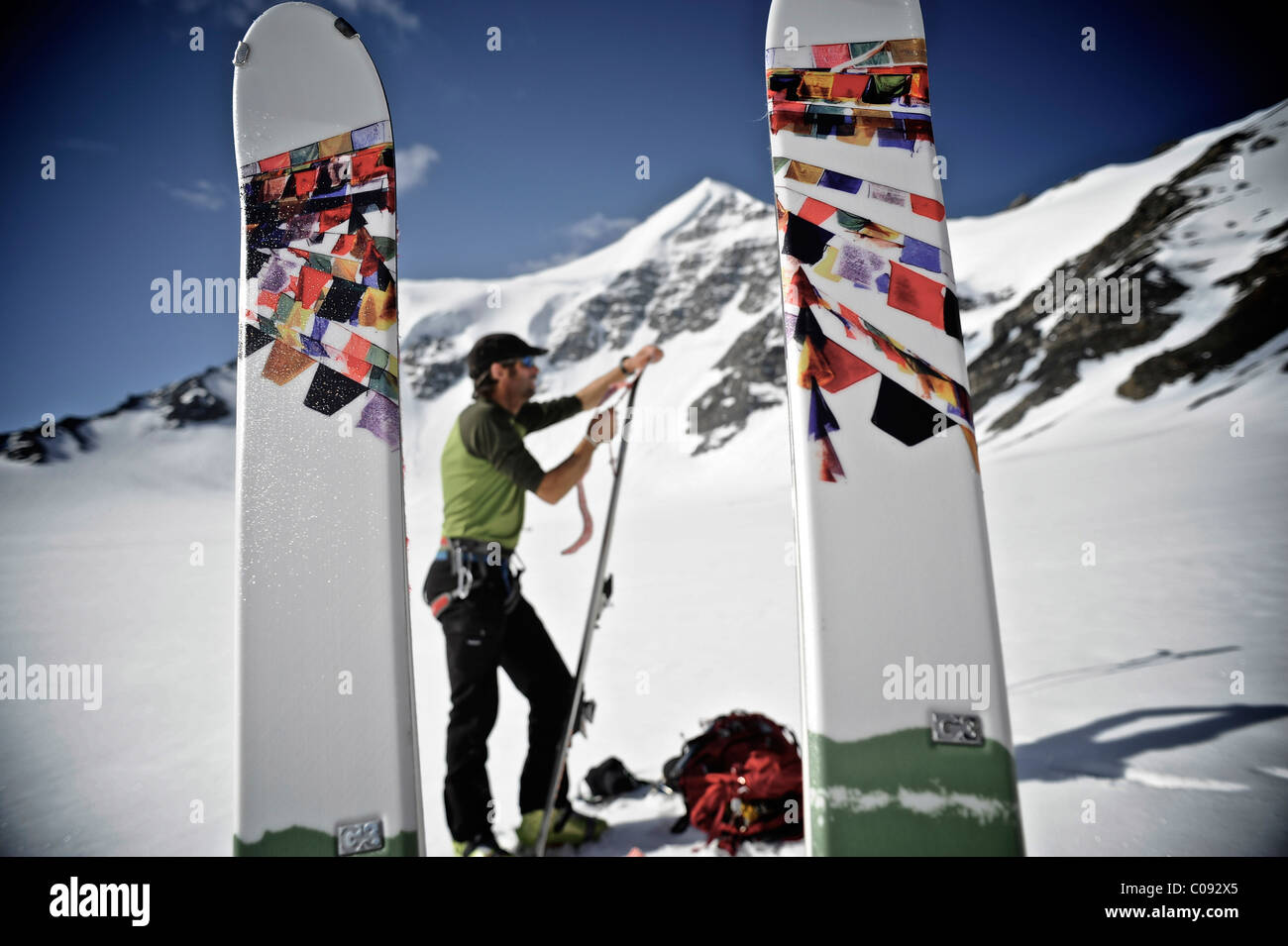 Backcountry skier prepares skis for descent of the north side of Mt. Chamberlin, Brooks Range, ANWR, Arctic Alaska, - Stock Image