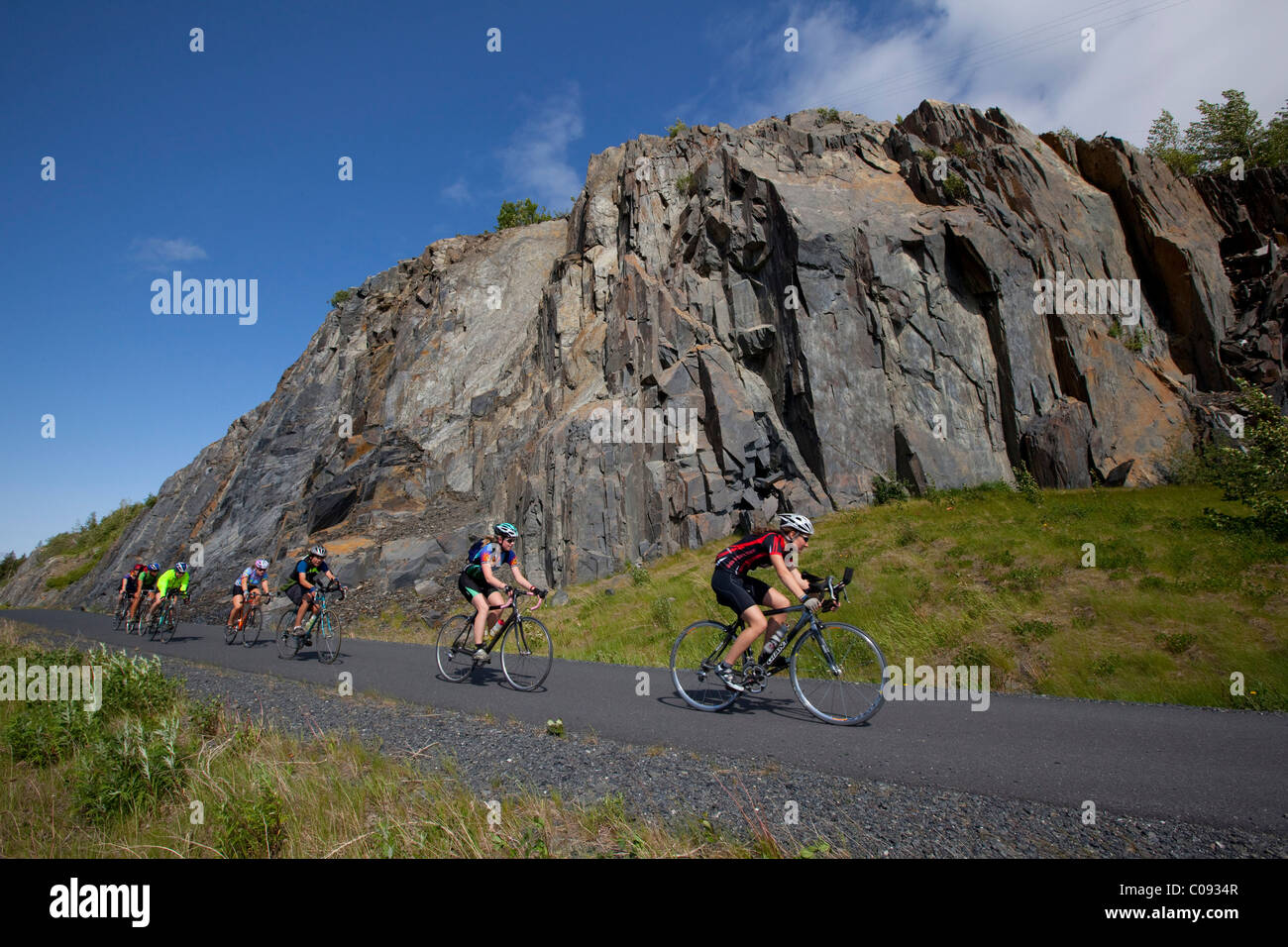 Group of bicyclists ride the bike trail next to Seward Highway towards Girdwood, Southcentral Alaska, Summer - Stock Image