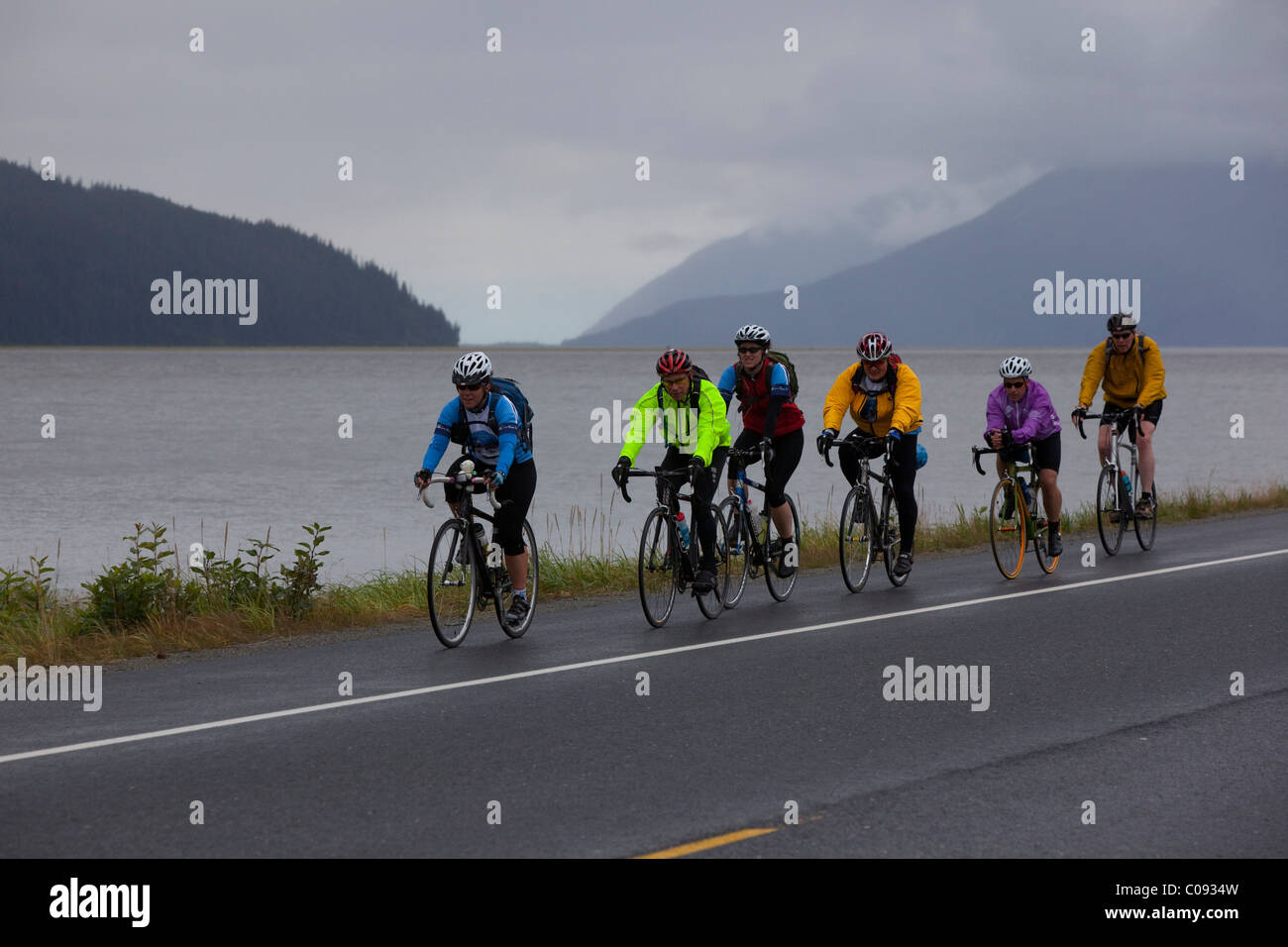 A group of bikers ride on the shoulder of the Seward Highway just south of Girdwood during a rainy weekend race - Stock Image