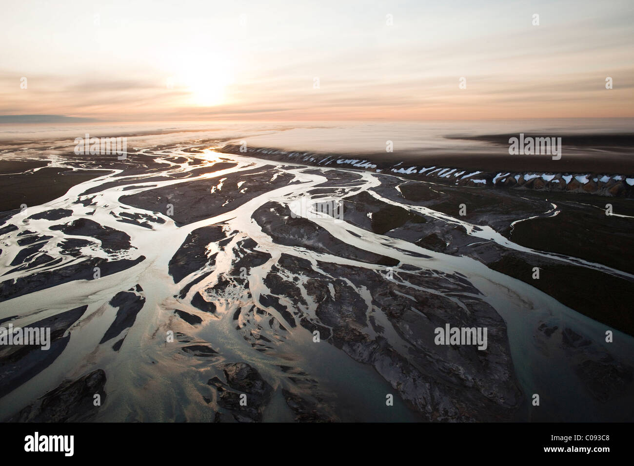 Aerial view of a sunrise over the Sagavanirktok River and fog hanging over the Franklin Bluffs near the Dalton Highway, - Stock Image