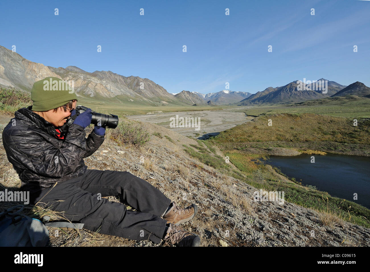 Woman photographs the Hulahula River near its source in the Brooks Range in ANWR, Arctic Alaska, Summer - Stock Image
