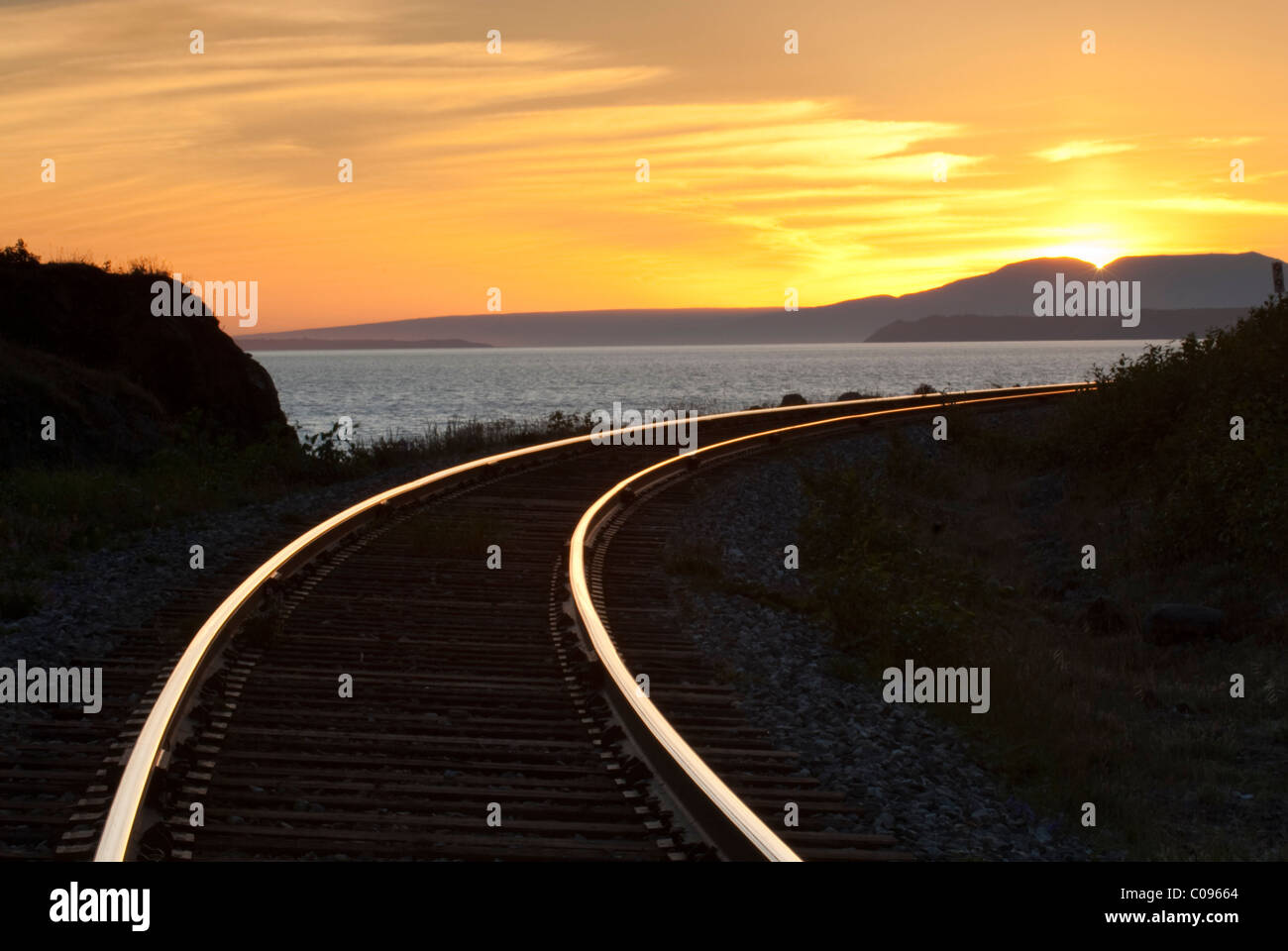The setting Summer sun reflects on train rails near Beluga Point along Turnagain Arm, Southcentral Alaska, Summer Stock Photo