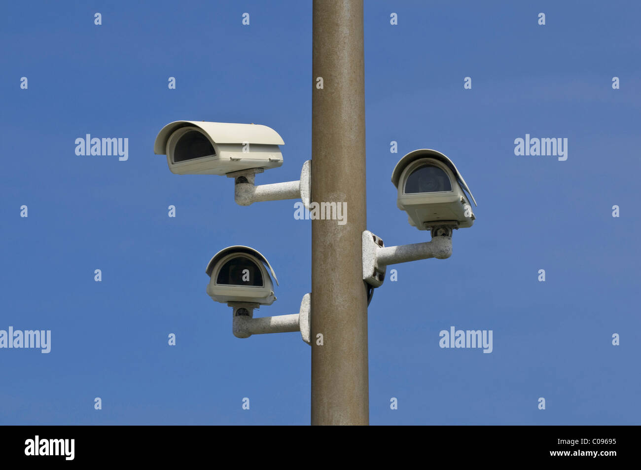 Three surveillance cameras on a post different viewing directions, street surveillance - Stock Image